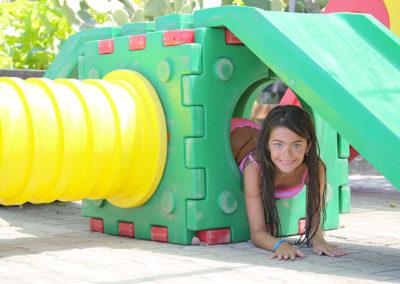 Bambina che esce da un gioco del villaggio