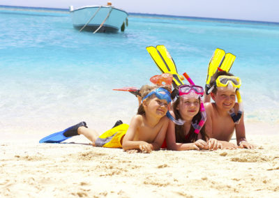 Bambini sorridenti con pinne e maschere in vacanza