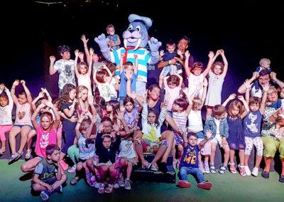 Animatori mascherati e bambini del villaggio turistico